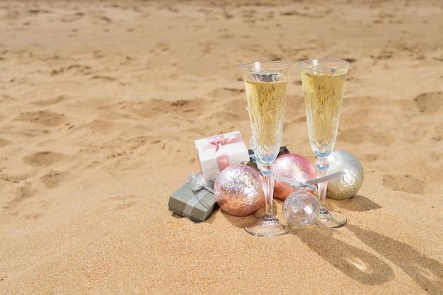 Due bicchieri di champagne natalizio con regali e decorazioni natalizie sulla sabbia della spiaggia