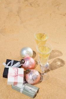 Due bicchieri di champagne natalizio con regali e decorazioni natalizie sulla spiaggia