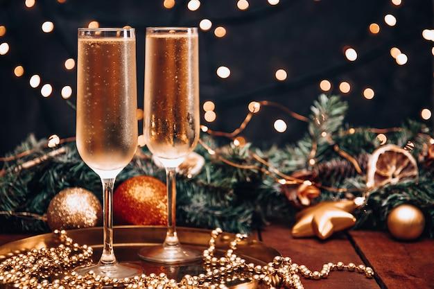 Due bicchieri di champagne freddo in un'atmosfera natalizia.