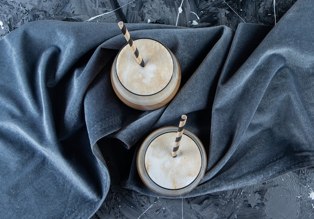 Due bicchieri di caffè freddo con latte sulla superficie di marmo.