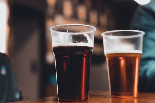Due bicchieri di birra scura e leggera su un tavolo in un pub, primo piano. messa a fuoco selettiva, sfocatura