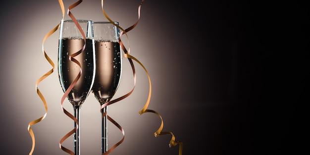 Due bicchieri pieni di champagne pronti per la festa. immagine su uno sfondo scuro con retroilluminazione e spazio di copia