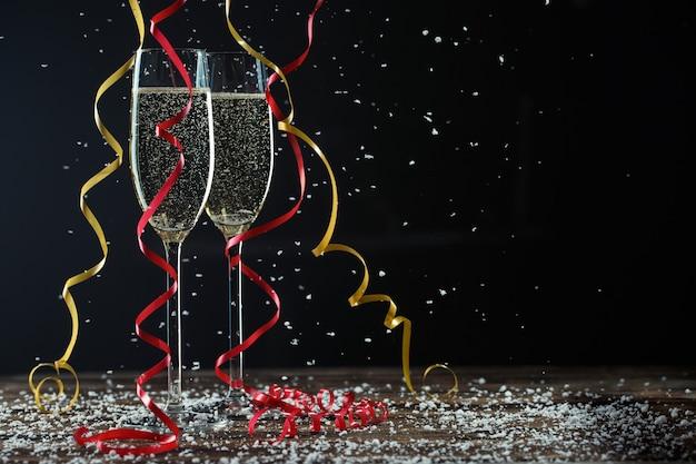 Due bicchieri di champagne frizzante su sfondo nero con bellissimi nastri e neve