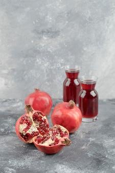 Due bicchieri di succo fresco con frutti di melograno maturi sulla superficie in marmo.