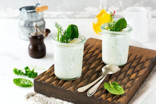 Due bicchieri di yogurt sano con una varietà di erbe, spinaci, aneto, cipolle, prezzemolo e uova di quaglia. il concetto di una sana colazione vegetariana. messa a fuoco selettiva.