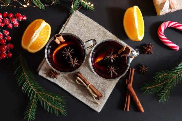Due bicchieri di vin brulé con cannella e arance su uno sfondo natalizio festivo