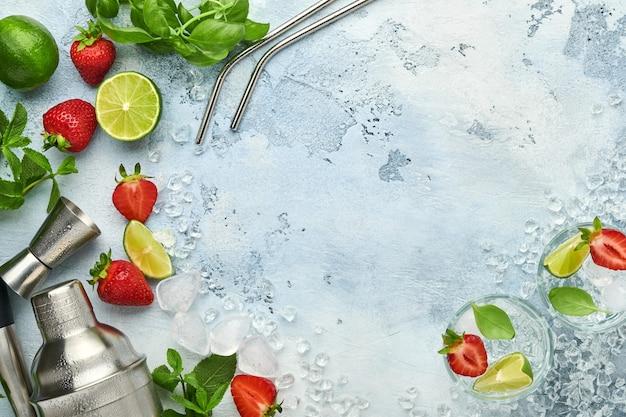 Due bicchieri di punch e ingredienti freschi per fare limonata, acqua detox infusa o cocktail. fragole, lime, menta, basilico, cubetti di ghiaccio e shaker su pietra grigia o fondo in cemento. vista dall'alto.