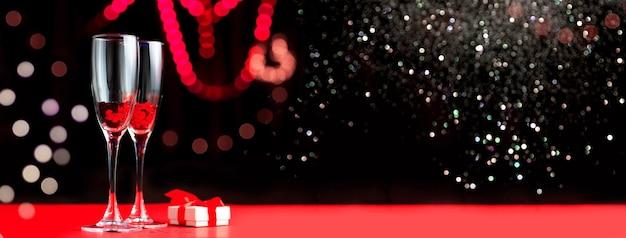 Due bicchieri di cuori rossi. accanto a loro c'è un regalo. fondo astratto di san valentino. bokeh sfocato in background. concetto di san valentino.