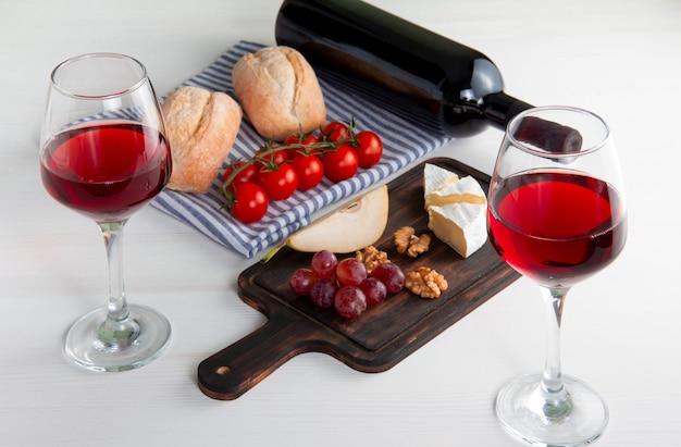 Due bicchieri di vino rosso, una bottiglia di vino rosso