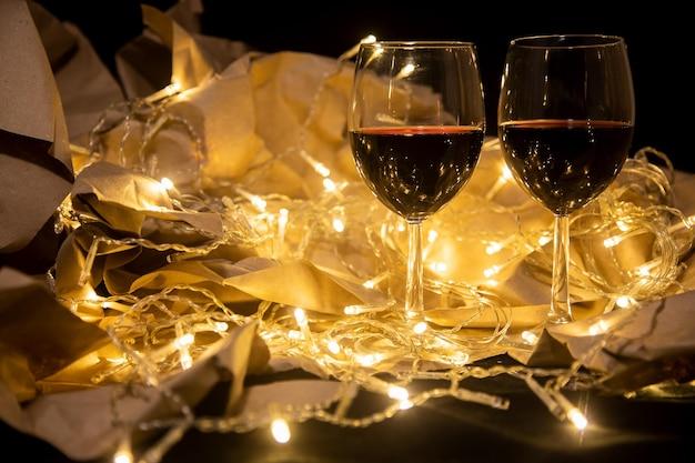 Due bicchieri di vino rosso stanno in una ghirlanda splendente