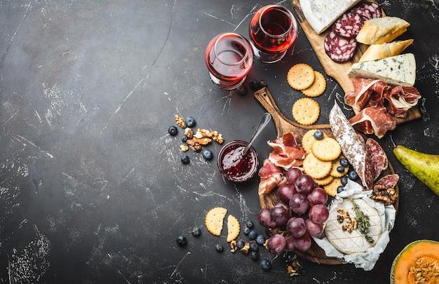 Due bicchieri di vino rosso, tavola di legno, salumi, formaggi, frutta, salsa. fondo in legno