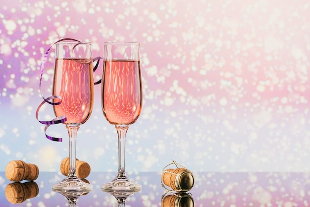 Due bicchieri di champagne rosa e decorazioni di natale o capodanno e tappi con un bokeh di luce dorata