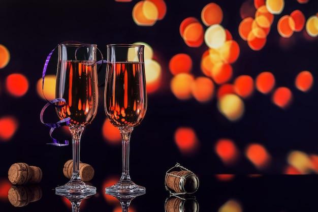 Due bicchieri di champagne rosa e decorazioni di natale o capodanno con un bokeh di luce dorata sul nero