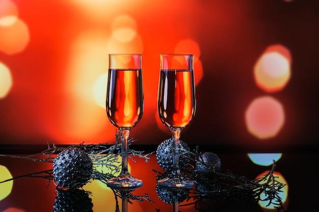 Due bicchieri di champagne rosa e decorazioni di natale o capodanno con un bokeh di luce dorata