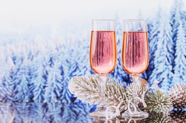 Due bicchieri di champagne rosa e decorazioni di natale o capodanno con bokeh foresta innevata di inverno