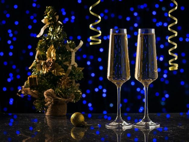 Due bicchieri di spumante e un albero di natale su luci bokeh blu. vigilia di capodanno