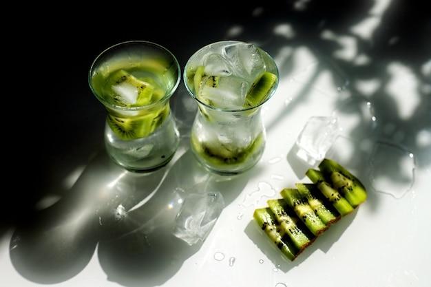 Due bicchieri stanno sul tavolo, i raggi del sole che cadono su di loro.