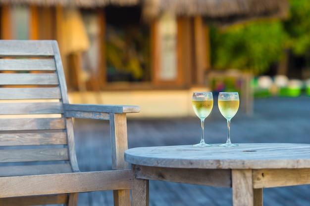 Due bicchieri di gustoso vino bianco al tramonto sul tavolo di legno