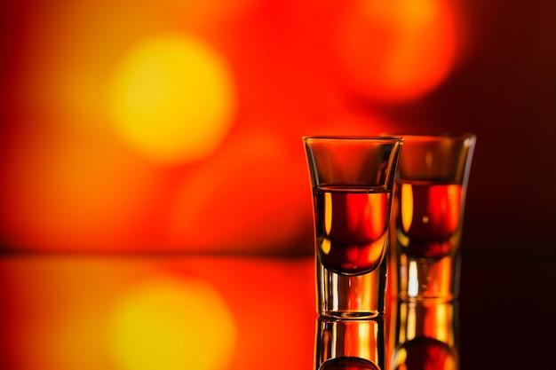 Due bicchieri di whisky o bourbon su un bokeh rosso