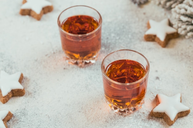 Due bicchieri di whisky o bourbon, biscotti a stella e decorazioni su sfondo bianco. concetto di umore del whisky invernale
