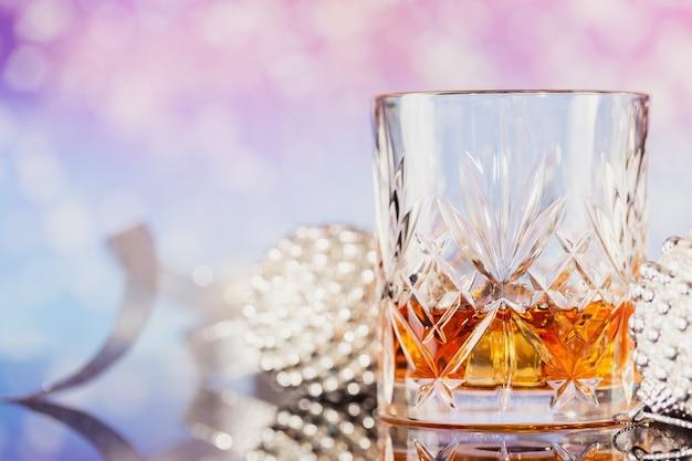 Due bicchieri di whisky o bourbon con decorazioni natalizie su uno sfondo bokeh chiaro. anno nuovo, natale e vacanze invernali concetto di umore del whisky
