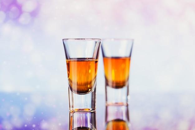 Due bicchieri di whisky o bourbon con decorazioni natalizie su un leggero bokeh