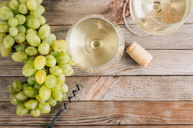 Due bicchieri di vino bianco e uva sulla tavola di legno d'epoca