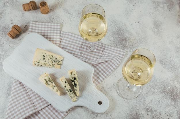 Due bicchieri di vino bianco serviti con tagliere di formaggi su superficie bianca. concetto di umore del vino.