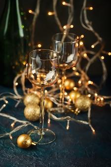 Due bicchieri di vino e palle di natale dorate contro luci dorate sfocate.