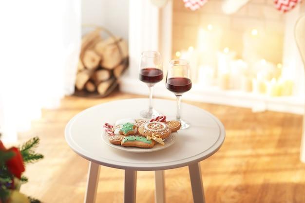 Due bicchieri di vino e un piatto di biscotti di natale sul tavolo in camera