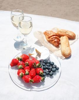 Due bicchieri di vino, fragole, formaggio, mirtilli e pane per un picnic sulla sabbia