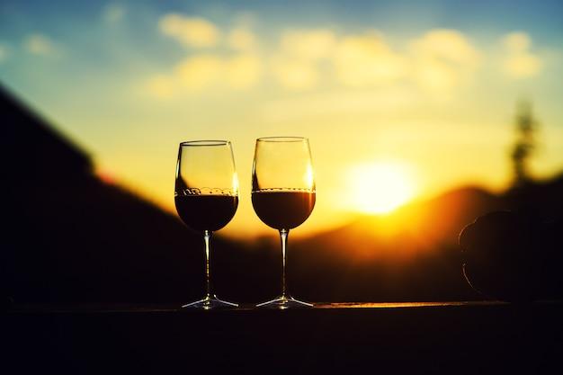 Due bicchieri di vino al tramonto cielo drammatico sullo sfondo del paesaggio di montagna