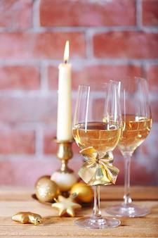 Due bicchieri di vino con candela e giocattoli di natale sulla superficie della parete
