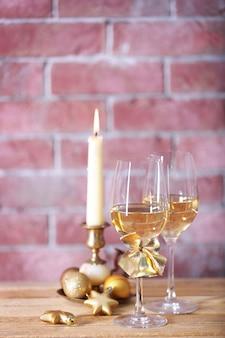 Due bicchieri di vino con candela e giocattoli di natale sul muro