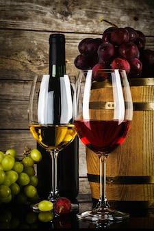 Due bicchieri di vino con uva fresca frash, bottiglia e botte davanti a vecchie tavole di legno del grunge