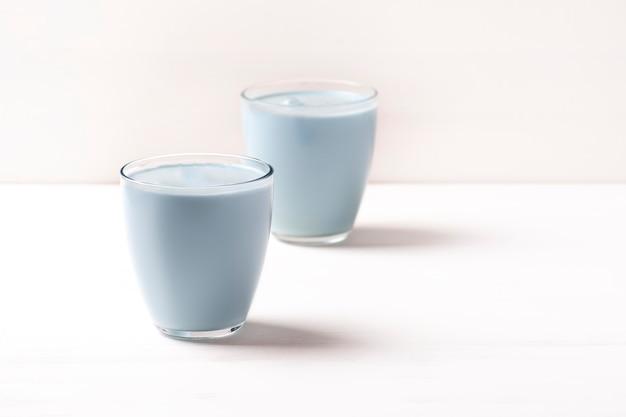 Due bicchieri con un matcha latte blu sono in piedi su un tavolo bianco