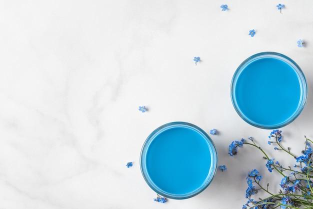Due bicchieri con matcha latte blu e non ti scordar di me fiori su fondo bianco