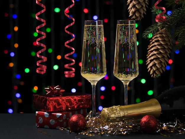 Due bicchieri con una bottiglia di champagne, regali e un albero di natale