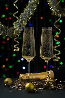 Due bicchieri con una bottiglia di champagne, stelle filanti e orpelli in una stanza buia