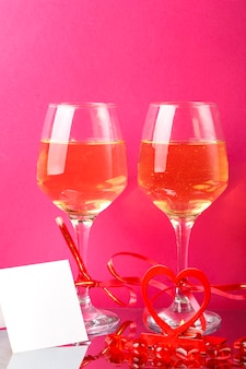 Due bicchieri di champagne legati con nastri rossi su una superficie rosa accanto a una cartolina