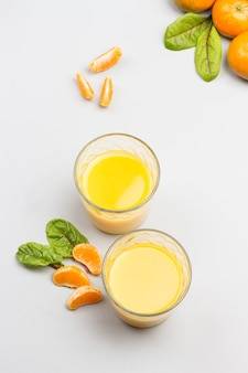 Due bicchieri con succo di agrumi. mandarini sul tavolo. lay piatto