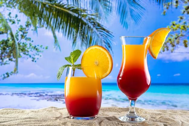 Due bicchieri con un drink sesso in spiaggia sulla sabbia e una spiaggia paradisiaca sullo sfondo