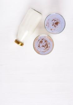 Due bicchieri con kefir fatto in casa e muesli con cannella sono su un tavolo di legno bianco