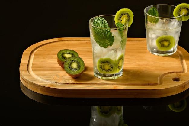 Due bicchieri con bevanda ghiacciata decorati con menta kiwi e ghiaccio su una tavola di legno isolata su un blac