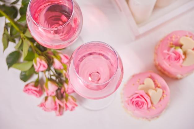 Due bicchieri di vino d'uva rosa con fiori di rosa e mini torte. concetto di cena romantica.