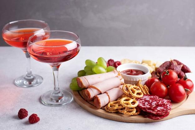 Due bicchieri con liquore rosso e tagliere rotondo di salumi con vari snack su sfondo grigio, festa un antipasto, primo piano.