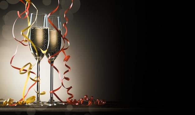Due bicchieri con champagne frizzante e nastri decorativi su sfondo nero con retroilluminazione e spazio copia