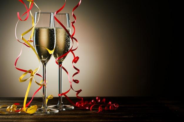 Due bicchieri con champagne frizzante e decorazioni festive. immagine isolata su sfondo nero con retroilluminazione e spazio di copia