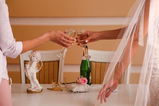 Due bicchieri di champagne frizzante in mano, matrimonio