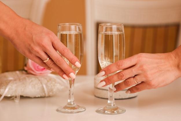 Due bicchieri di spumante champagne nelle mani, concetto per il matrimonio